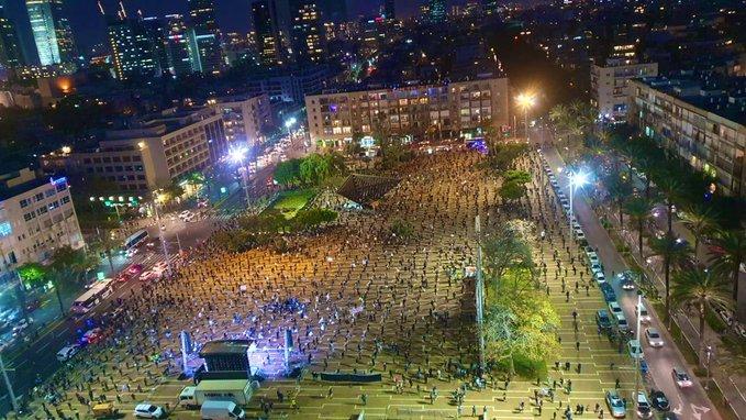 Manifestantes a un metro de distnacia formando una retícula, de noche y visto desde arriba. Sucede en una gran ciudad: Tel Aviv